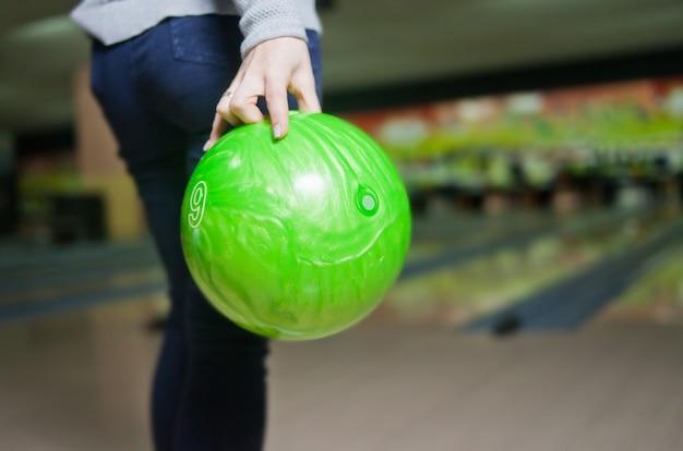 De hand van de vrouw houdt groene kegelenbal klaar te werpen