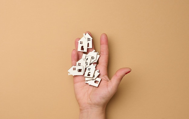De hand van de vrouw houdt miniatuur houten huizen vast. zoekconcept voor onroerend goed voor huur, hypotheek, onroerendgoedverzekering