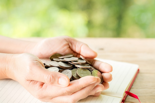 De hand van de vrouw houdt veel munten vast