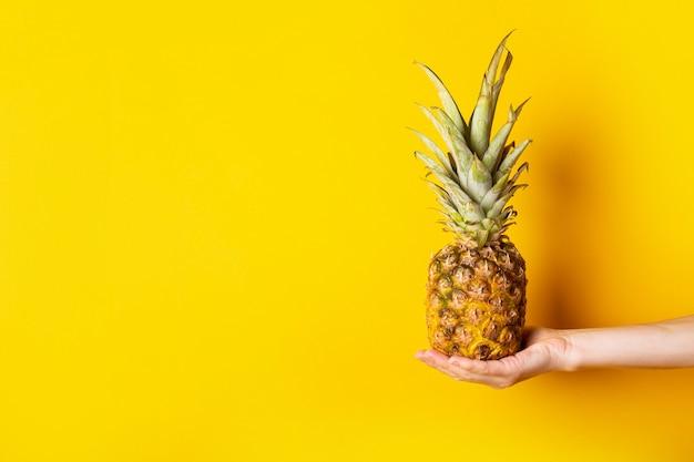 De hand van de vrouw in de palm houdt een hele ananas op een gescheurde gele achtergrond.