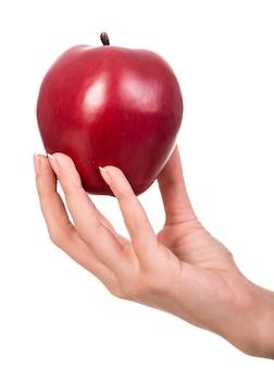 De hand van de vrouw met een geïsoleerde appel