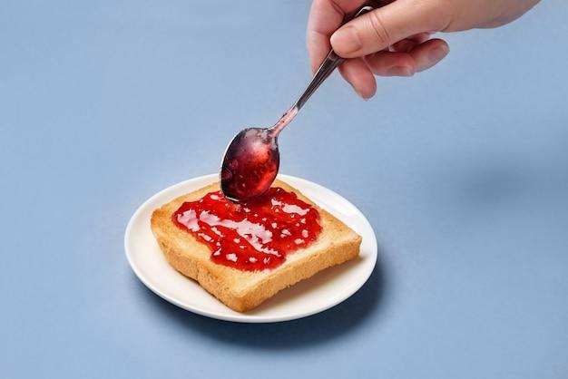 De hand van de vrouw met een lepel verspreidt frambozenjam op gebraden toostclose-up. het concept van een heerlijk ontbijt.
