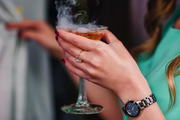 De hand van de vrouw met een martiniglas met bellen en stoom