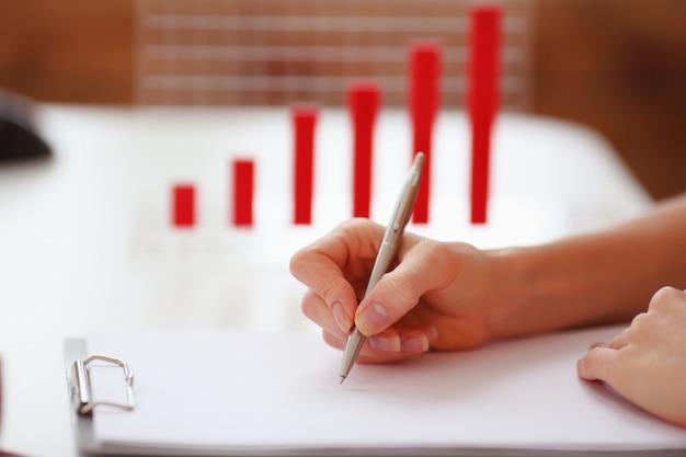 De hand van de vrouw met een pen die op een blad van document op de achtergrondgrafiek schrijft