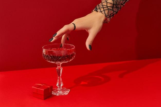 De hand van de vrouw met griezelig nagelontwerp neemt glas met cranberry-halloween-cocktail op rode achtergrond