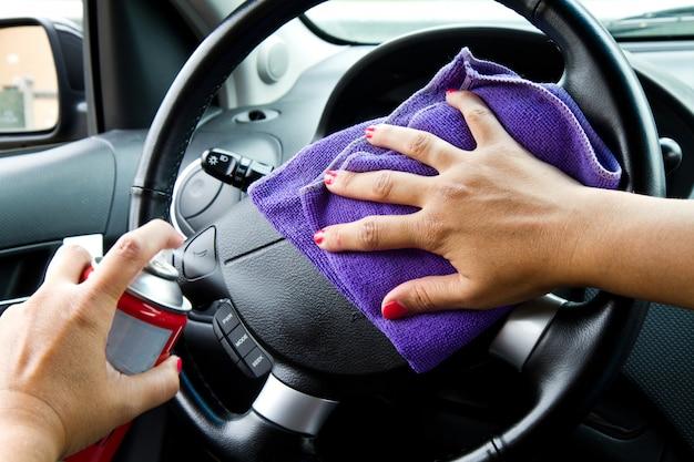 De hand van de vrouw met het oppoetsende wiel van de microfiberdoek van een auto