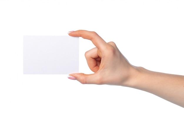 De hand van de vrouw met leeg wit adreskaartje dat op wit wordt geïsoleerd
