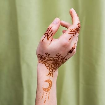 De hand van de vrouw met mehndi schildert dichtbij textiel