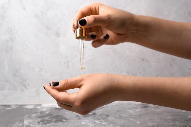 De hand van de vrouw met pipet en olie cosmetisch product