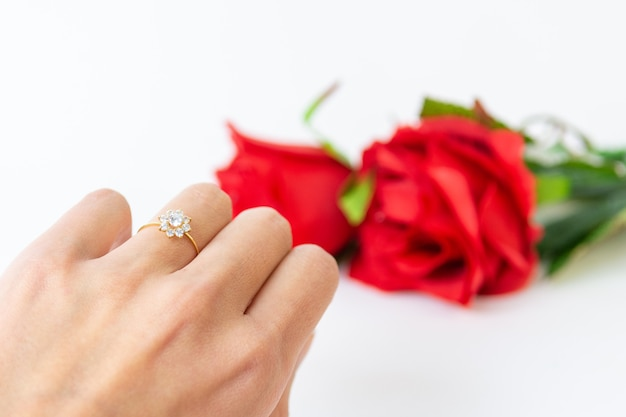 De hand van de vrouw met ring en rozen voor valentijnsdag