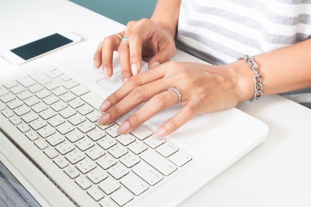 De hand van de vrouw met trouwring die laptop computer met behulp van. technologie en levensstijlconcept