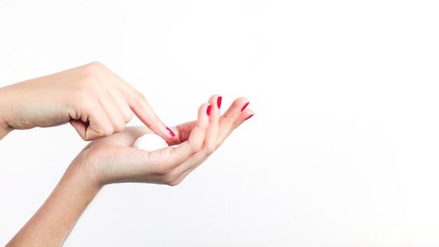 De hand van de vrouw met vochtinbrengende crème op witte achtergrond wordt geïsoleerd die