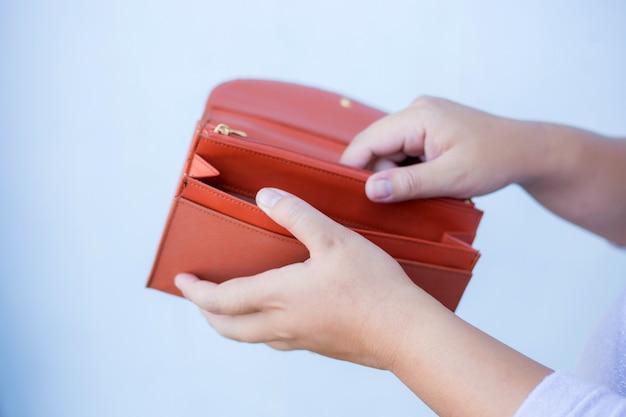 De hand van de vrouw opent een lege portefeuille