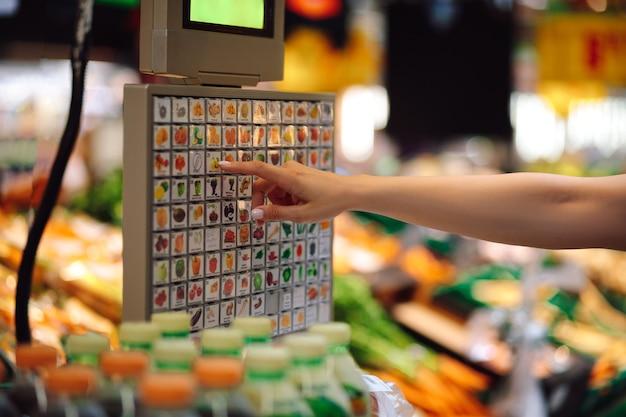 De hand van de vrouw selecteert de gewenste positie op het display van elektronische weegschalen in de groenteafdeling van de supermarkt. organisatie van de handel. moderne technologieën. gemak en zelfbediening.