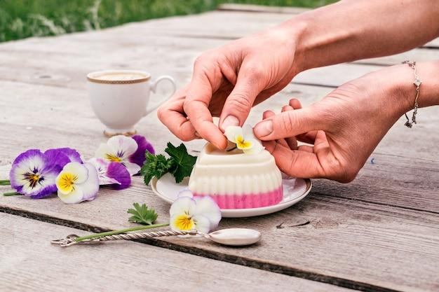 De hand van de vrouw siert een hartvormige wrongelsoufflé met een bloem. concept van gezonde voeding