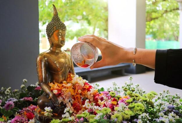 De hand van de vrouw sprenkelt water op een boeddha-figuur