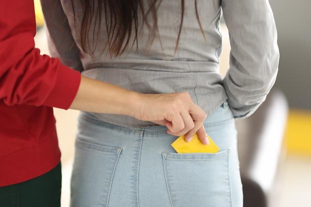 De hand van de vrouw steekt condoom in de broekzak van een andere vrouw.