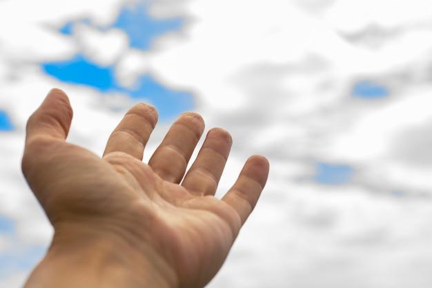 De hand van de vrouw strekt naar de hemel