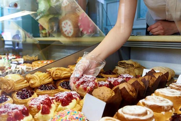 De hand van de vrouw van de verkoper in een handschoen neemt de taart uit de vitrine.