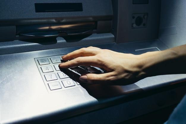 De hand van de vrouw voert de geheime code in bij de geldautomaat op straat 's nachts