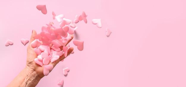 De hand van de vrouw werpt roze satijnen harten op roze. concept liefde. vrouw geeft haar liefde aan de hele wereld.
