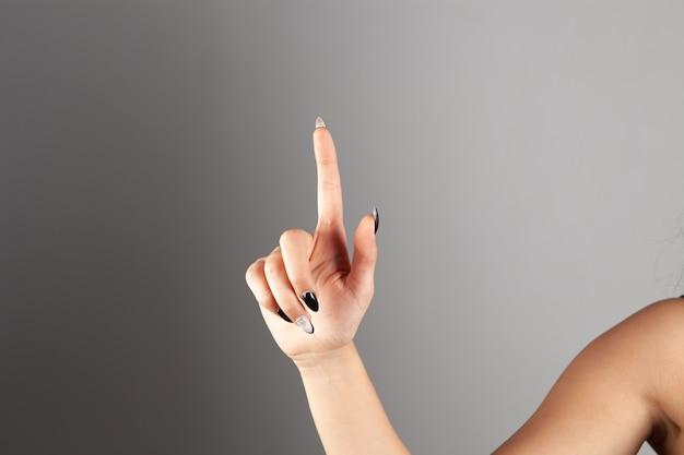 De hand van de vrouw wijst een vinger omhoog