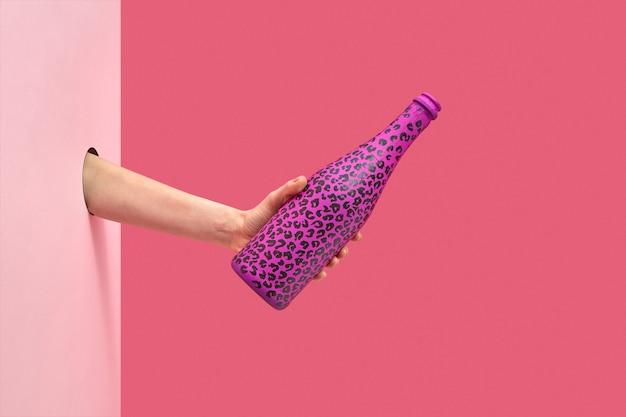 De hand van de vrouw wil wijn schenken uit een geschilderde chanpagne-fles met zwarte vlekken op een duotone roze achtergrond, kopieer ruimte. vakantie-concept.