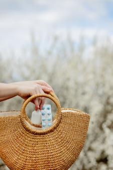 De hand van de vrouw zet allergiepillen in zak op bloeiende achtergrond