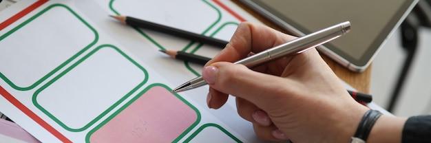 De hand van de vrouw zet een stempel op de ontwikkeling van de kadastrale kaart en de planning van percelen voor huisvesting