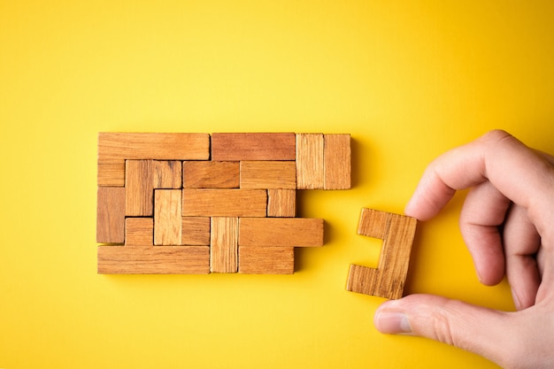De hand van de vrouw zet houten blokken voor het beëindigen van taak