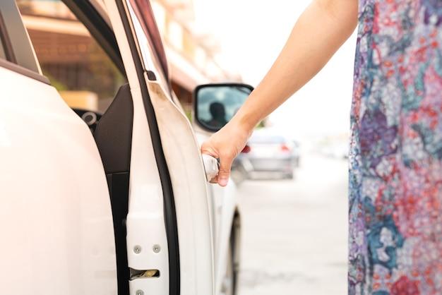 De hand van de vrouwenbestuurder opent de autodeur
