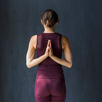 De hand van de vrouwenholding achter haar terug in een het bidden positie