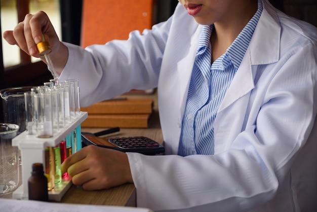 De hand van de wetenschapper laat chemische vloeistof aan buis vallen