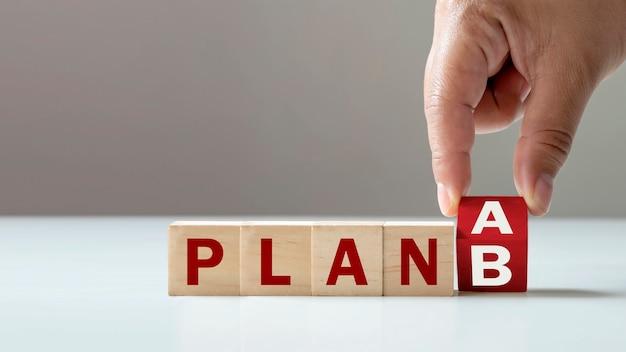 De hand van de zakenman draait houten kubusblokken van plan a naar plan b oplossingsideeën voor mkb-organisaties