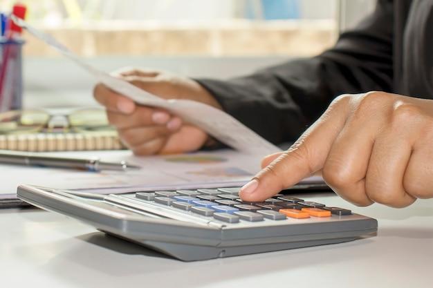 De hand van de zakenman drukt op een rekenmachine, doet financieel werk en berekent op de tafel over uitgaven op kantoor aan huis.