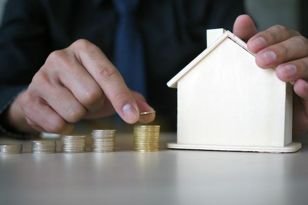 De hand van de zakenman houdt een muntstuk in een stapel en legt het huismodel vast.