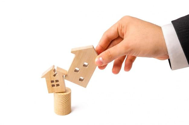 De hand van de zakenman vervangt het oude huis door een beschadigd huis voor een nieuw huis.