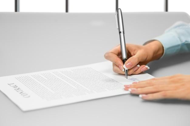 De hand van de zakenvrouw ondertekent een document. ondertekeningspapier op witte achtergrond. eén stap zorgt voor veel veranderingen. denk na voordat je verder gaat.