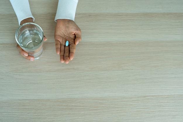 De hand van de zieke vrouw hield het medicijn of de pillen vast.