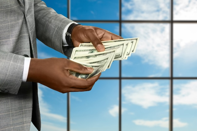 De hand van de zwarte zakenman telt geld. geld tellen op de hemelachtergrond. het fortuin in zijn handen. geniet zolang het kan.