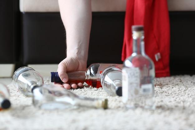 De hand van een alcoholist houdt de helft vast