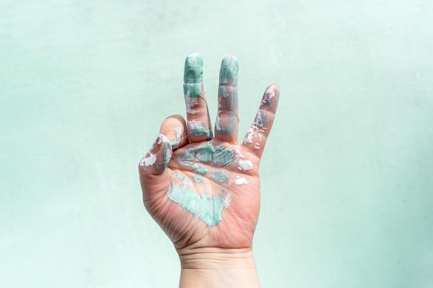 De hand van een arbeider in verf toont een ok teken met zijn vingers tijdens het schilderen van een muur.