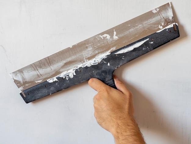 De hand van een arbeider met een lange spatel die aan de muur werkt. binnenwerk, bouwconcept