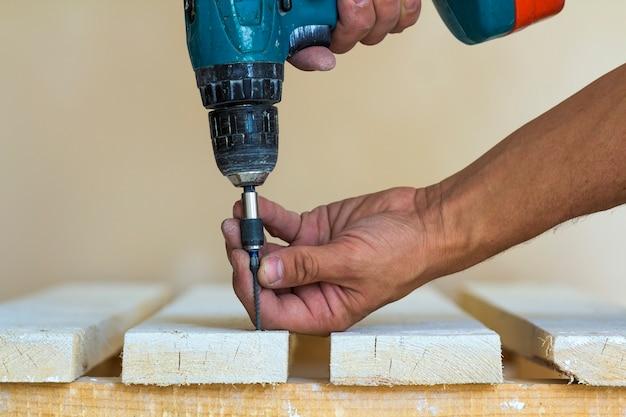 De hand van een arbeider schroeft een schroef in een houten raad met een draadloze schroevedraaier