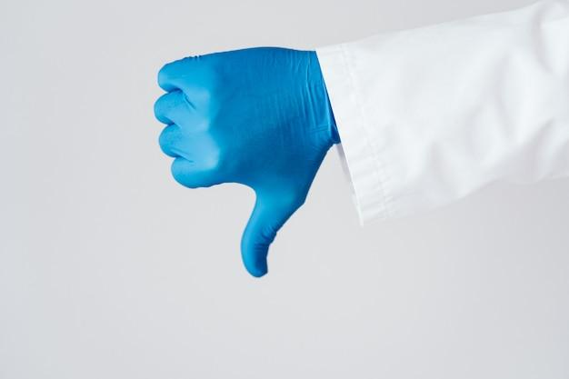 De hand van een arts in blauwe handschoen die afkeuring toont, beduimelt neer
