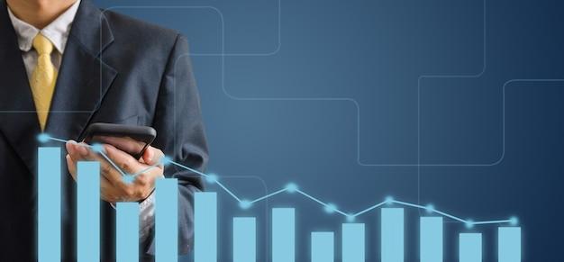 De hand van een bedrijfsmens houdt een mobiele telefoon op een grijze achtergrond. analyseer grafieken en diagrammen van bedrijfsgroei. kopieer ruimte