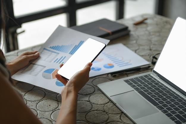 De hand van een bedrijfsvrouw gebruikt een mobiele telefoon om informatie te vinden.