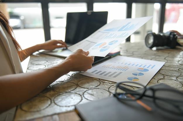 De hand van een bedrijfsvrouw gebruikt laptop om informatie te vinden