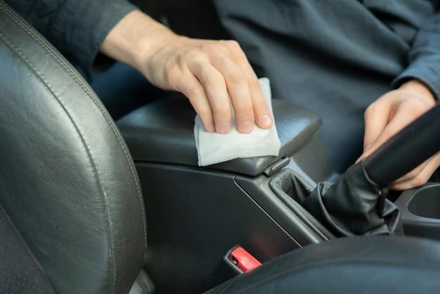 De hand van een bestuurder die een microvezel vasthoudt en het auto-interieur van binnen afveegt