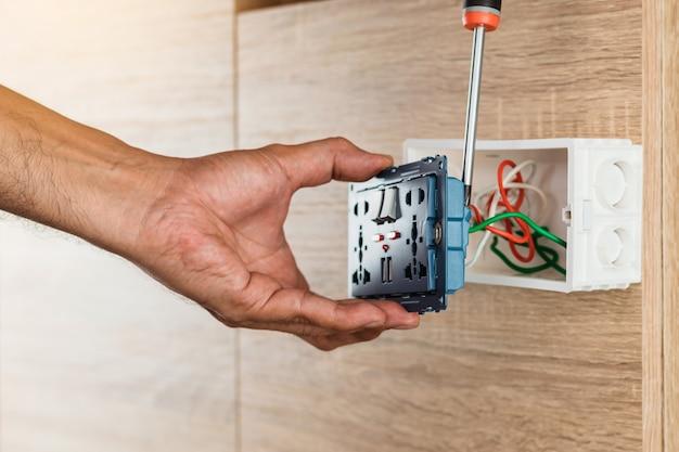 De hand van een elektricien gebruikt een schroevendraaier om de draden aan de universele stopcontact ac-stekker met usb-poort en aan-uit in een plastic doos op een houten muur te bevestigen.